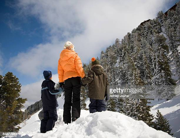 Mother with two boys (6-9) looking at view in snow