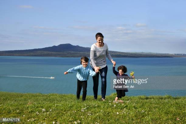 Mother with two daughters running together on green grass outdoors
