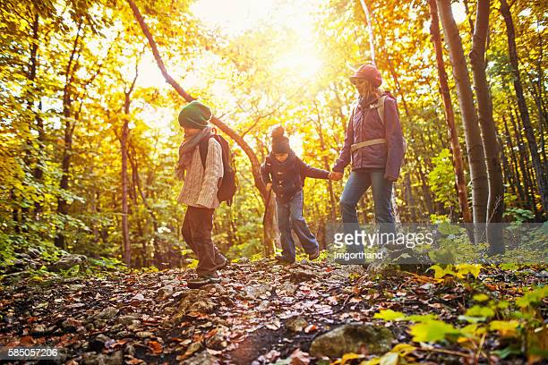 Mother with two kids hiking in autumn forest
