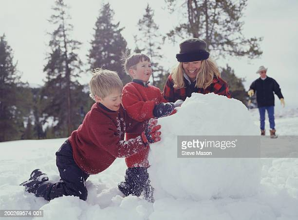 Mother with two sons (8-9) making snowman