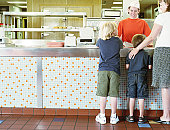 Mother with two sons ordering from fast-food counter, rear view