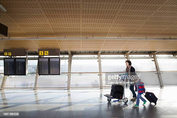 mother with young son and luggage at airport