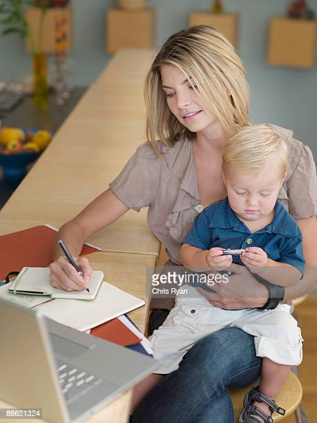Mother working and holding son on lap