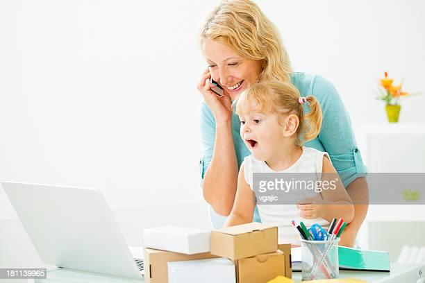 Mère travaillant à la maison avec bébé.