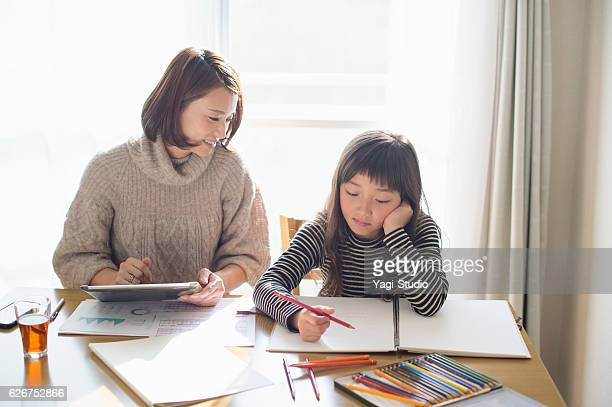 Mother working at home with daughter