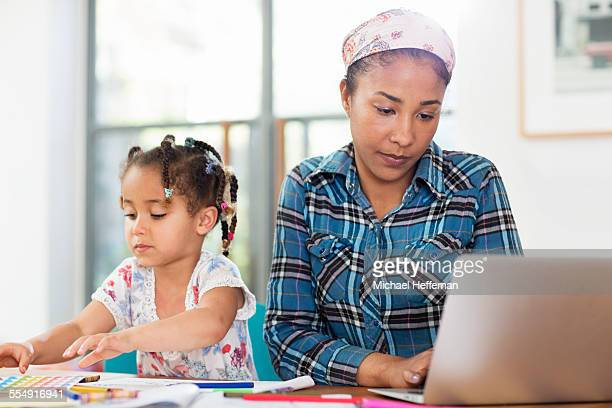 Mother working at table as daughter plays