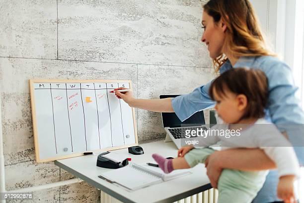 Mãe a trabalhar a partir de casa e segurar o seu bebé
