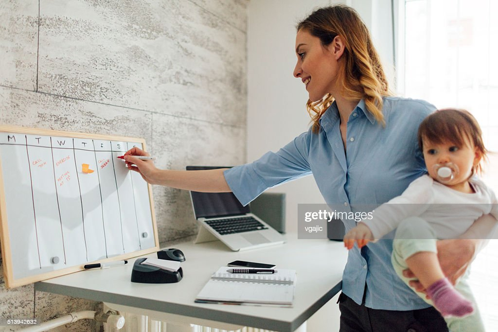 Mother Working From Home And Holding Her Baby : Stock Photo