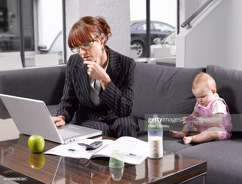 Mother working on laptop, baby boy (6-11 months) playing with toys : Stock Photo