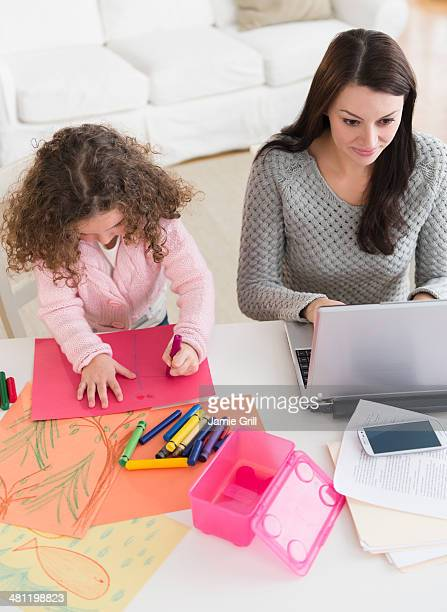 Mother working on laptop, daughter coloring