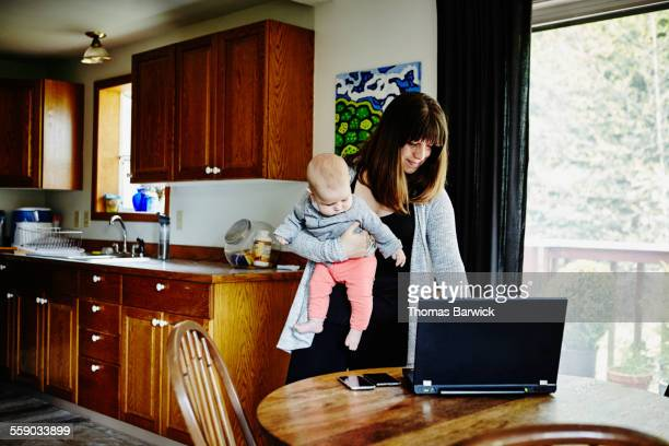 Mother working on laptop holding infant daughter