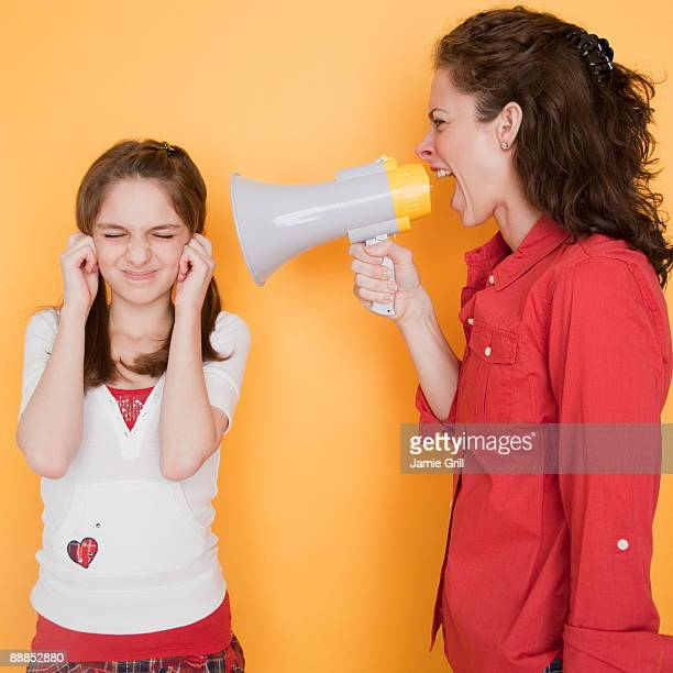 Mother yelling at daughter (10-11 years) through megaphone