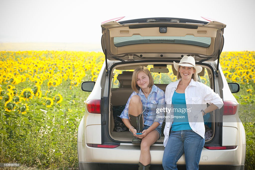 Mother/daughter farmers in sunflower field : Stock Photo