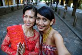 A mother and daughter dressed up in traditional Indonesian clothes taking a selfie.
