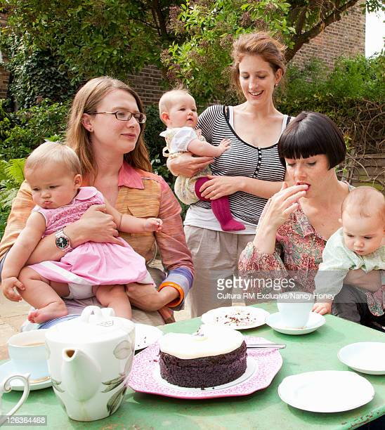 Mothers and babies having tea outdoors