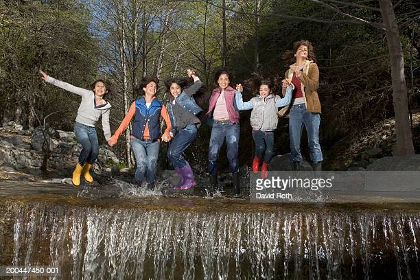 Mothers and daughters (10-13) jumping in river over waterfall