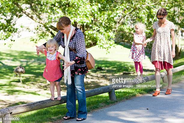 Mothers assisting daughters walking on railing at zoo