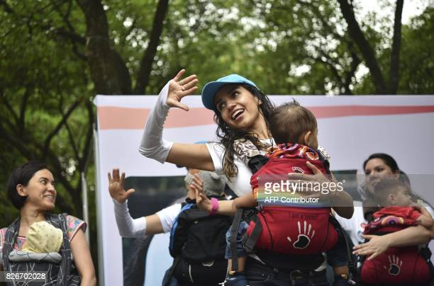 Mothers carrying their children perform during the 'Big Latch On' breastfeeding festival held at the Bonatic Garden of the Chapultepec Park in Mexico...