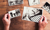 Mothers day composition. Hands of unrecognizable man holding  black-and-white photos. Studio shot on wooden background.