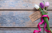 Mothers day label attached to spring tulips with decorative ribbon