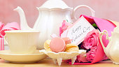 Happy Mother's Day tea setting with teapot, macaron cookies, pink roses and gift close up.