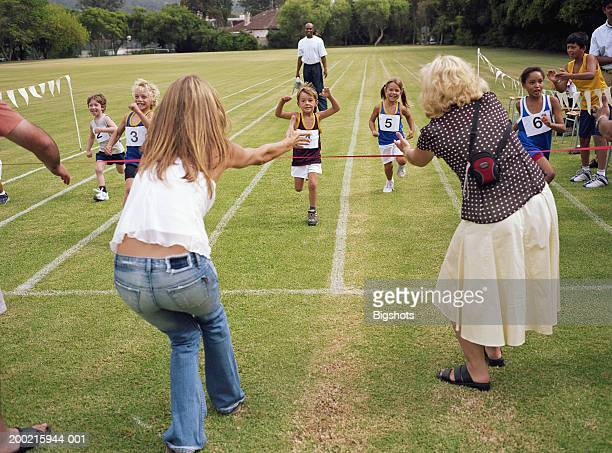 Mothers encouraging children (4-9) reaching finish line of race