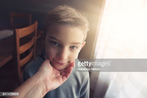 mother's hand cupping son's chin