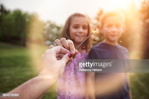 mother's hand holding out sparkler to kids