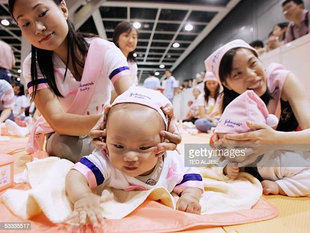 Mothers rub their children during a baby massage contest as part of an international baby products fair at the Hong Kong Convention and Exhibition...
