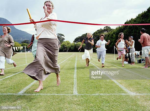 Mothers running relay race at school sports day, smiling