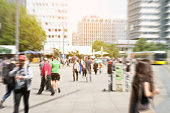 picture with motion blur of a crowd of people crossing a city street at the pedestrian zone