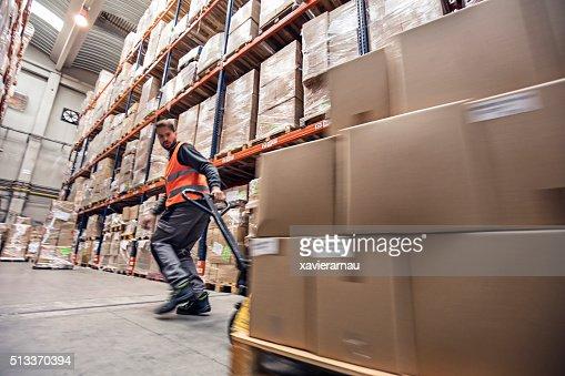 Borrão de movimento de um homem movendo caixas em armazém