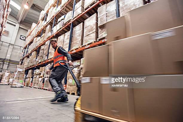 Movimiento desenfoque de un hombre moviendo cajas en un almacén