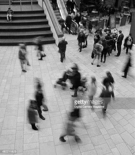 Motion blur of shoppers walking around Cabot Circus shopping centre in Bristol England on December 2 2012