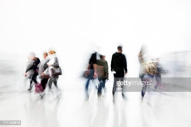 Motion Blurred Pedestrians Walking in White Hallway