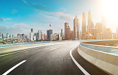 Motion curvy flyover asphalt highway road with modern cityscape skyline view  . Sunrise scene .