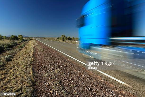 Motion photo of a speeding blue truck on the freeway