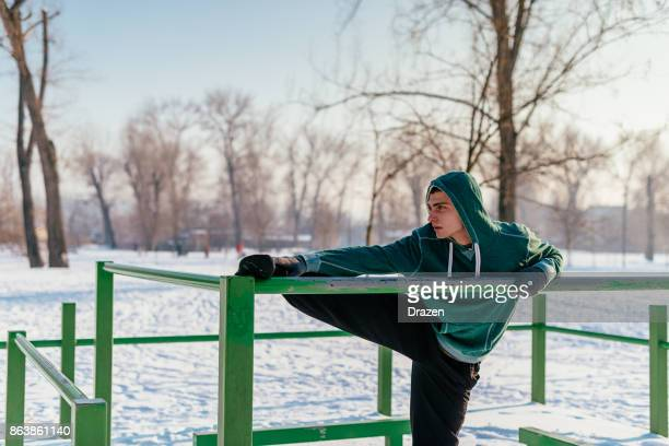 Motivated athlete exercising on cold winter day outdoors