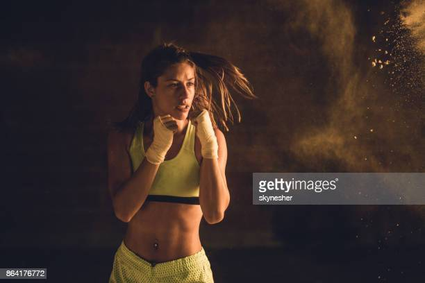 Motivated female athlete in motion on a boxing training.