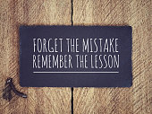 'Forget the mistake, remember the lesson' written on a black piece of paper with background of wooden wall.