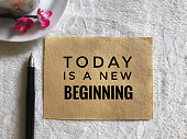 'Today is a new beginning' on an old white piece of paper. With vintage styled background.