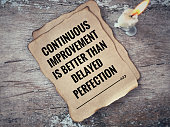 'Continuous improvement is better than delayed perfection' on a piece of paper. With blurred vintage styled background.