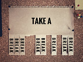 'Take a break' written on a white paper that sticked on a wall. With vintage styled background.