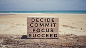 'Decide, commit, focus, succeed' on a wooden blocks. With vintage styled background.