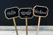 Motivational message Hello Weekend written with chalk on wooden mini blackboard labels, defocused chalkboard and wood table in background