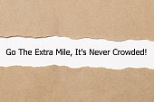 Motivational quote Go The Extra Mile It's Never Crowded appearing behind ripped paper.