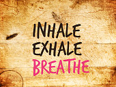 Motivational text saying  INHALE EXHALE BREATHE on a grunge wood surface. Mantra for zen and relaxation exercises. Advice for coping with stress and staying in the moment.