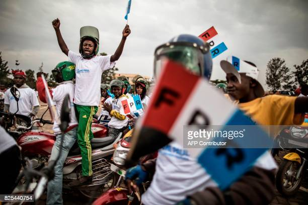 TOPSHOT Moto taxi driver hold flags of the governing Rwanda Patriotic Front's at the beginning of a parade in Kigali on August 02 2017 Incumbent...