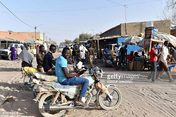 Moto taxi drivers wait in a market of the central Niger city of Agadez on May 29 2015 AFP PHOTO / ISSOUF SANOGO
