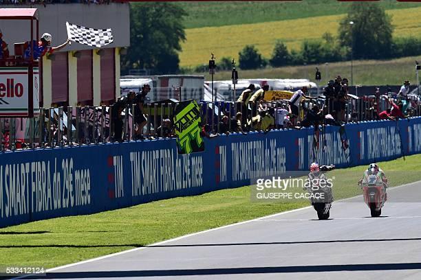 Moto2 rider French Johann Zarco crosses the finish line ahead of Italian Lorenzo Baldassarri during the Moto2 race as part of the Italian Moto Grand...